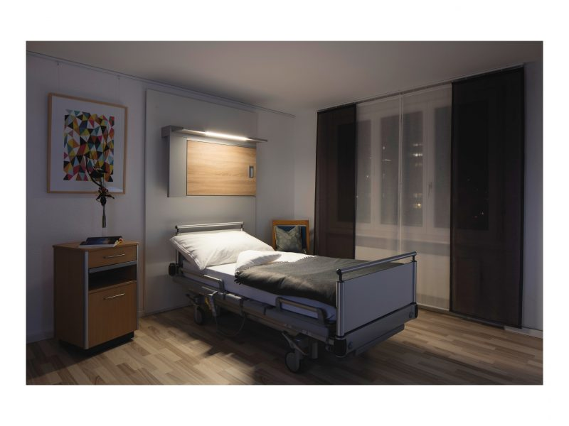 An evening time Aged Care bedroom setting showing the HPA Derungs Zera Bed Wall Mounted Light with Circadian Lighting Visual Timing Light activated