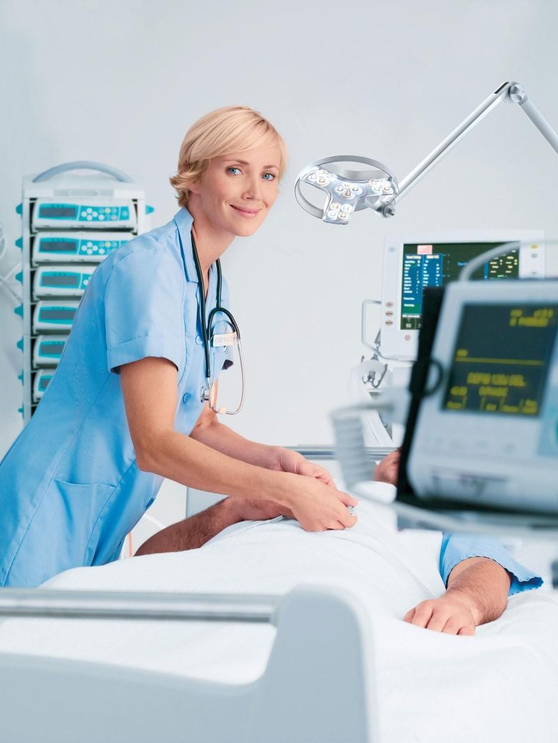 A nurse or doctor using a Derungs Visiano 20-2 Examination Light - Spring Balanced Arm