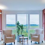 Image of Derungs Wall Mounted Lights in an aged care corridor with 2 arm chairs and a window out to field. The light has Circadian Lighting Visual Timing Light enabled