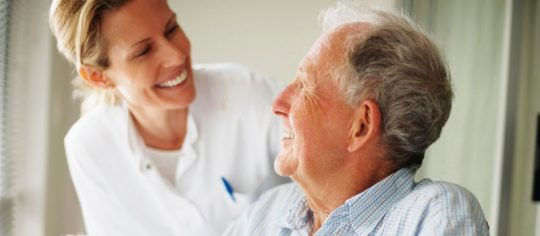 An elderly man looking up at a female nurse under the glow of circadian lighting visual timing light aged care lighting by Derungs