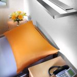 View of a HPA Derungs Zera Bed Wall Mounted Light mounted above a bed with an orange pillow